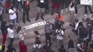 デモ行進の横断幕に中国語・暴動の背後に中国が