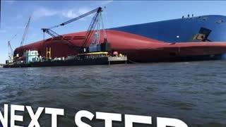 転覆した韓国の自動車運搬船ゴールデンレイ周辺にオイルブームを設置するクルー