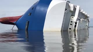 転覆した韓国の貨物船ゴールデンレイの周りに防護壁を構築する作業員
